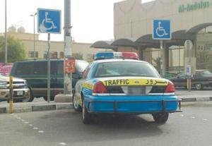 سيارة شرطة تقف في مواقف المعاقين