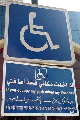 لوحة ارشادية متعددة اللغات تشير الي انه موقف خاص للمعاقين